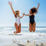 Two funny girls with beautiful bodies in swimwear jumping on a tropical beach. Funny caucasian and arabic females wearing black and white swimsuits.
